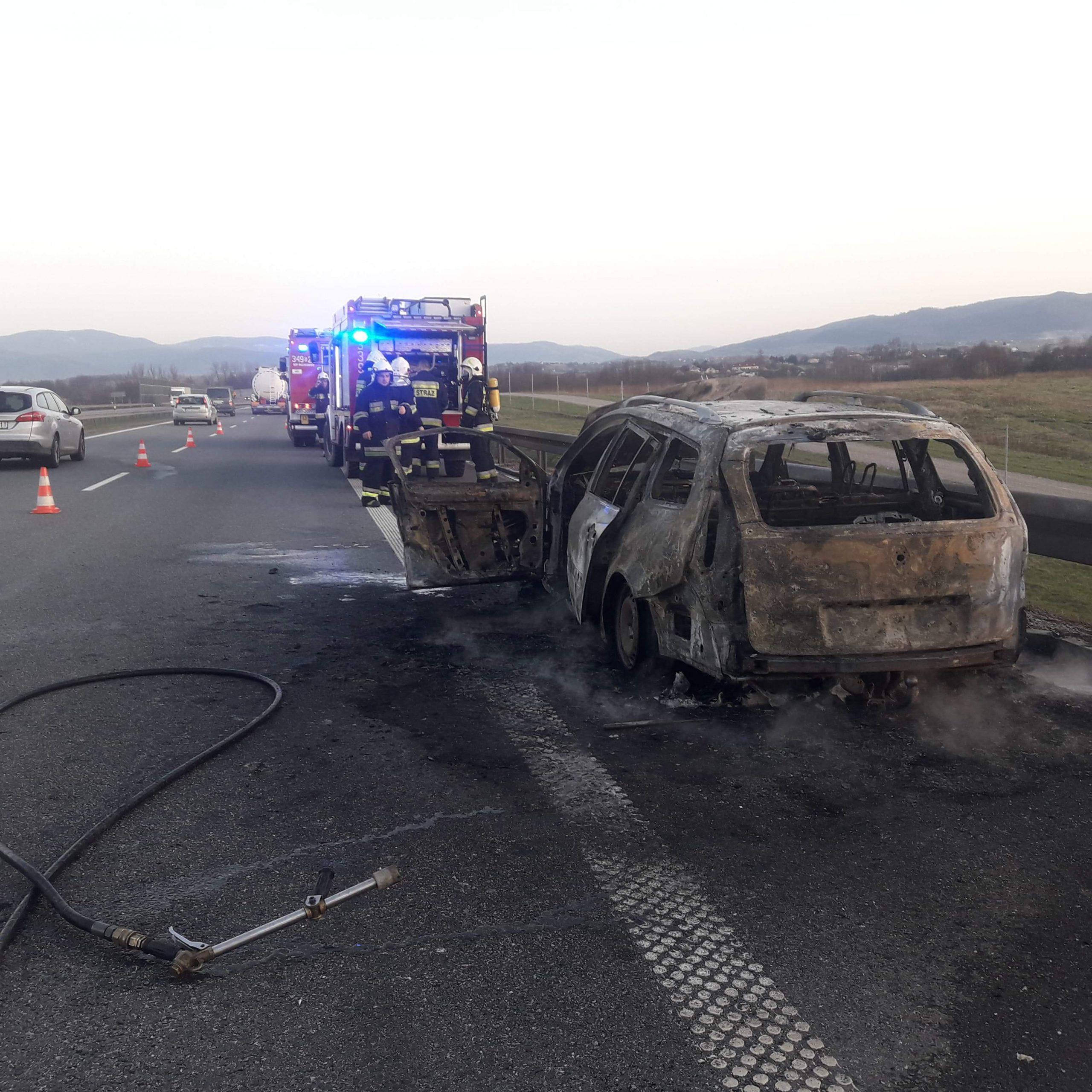 Akcja ugaszania płonącego pojazdu - na zdjęciu samochody strażackie, strażacy oraz doszczętnie spalony samochód