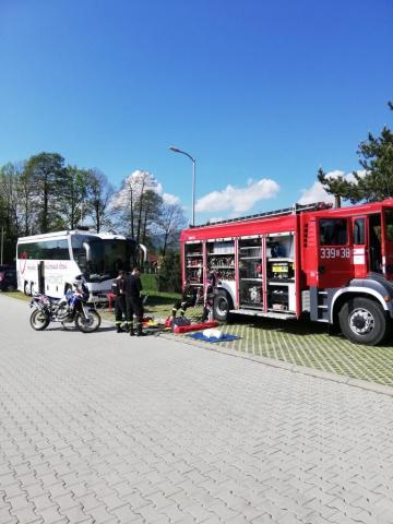 strażacy rozkładają przed wozem strażackim rekwizyty do ćwiczeń z udzielania pierwszej pomocy