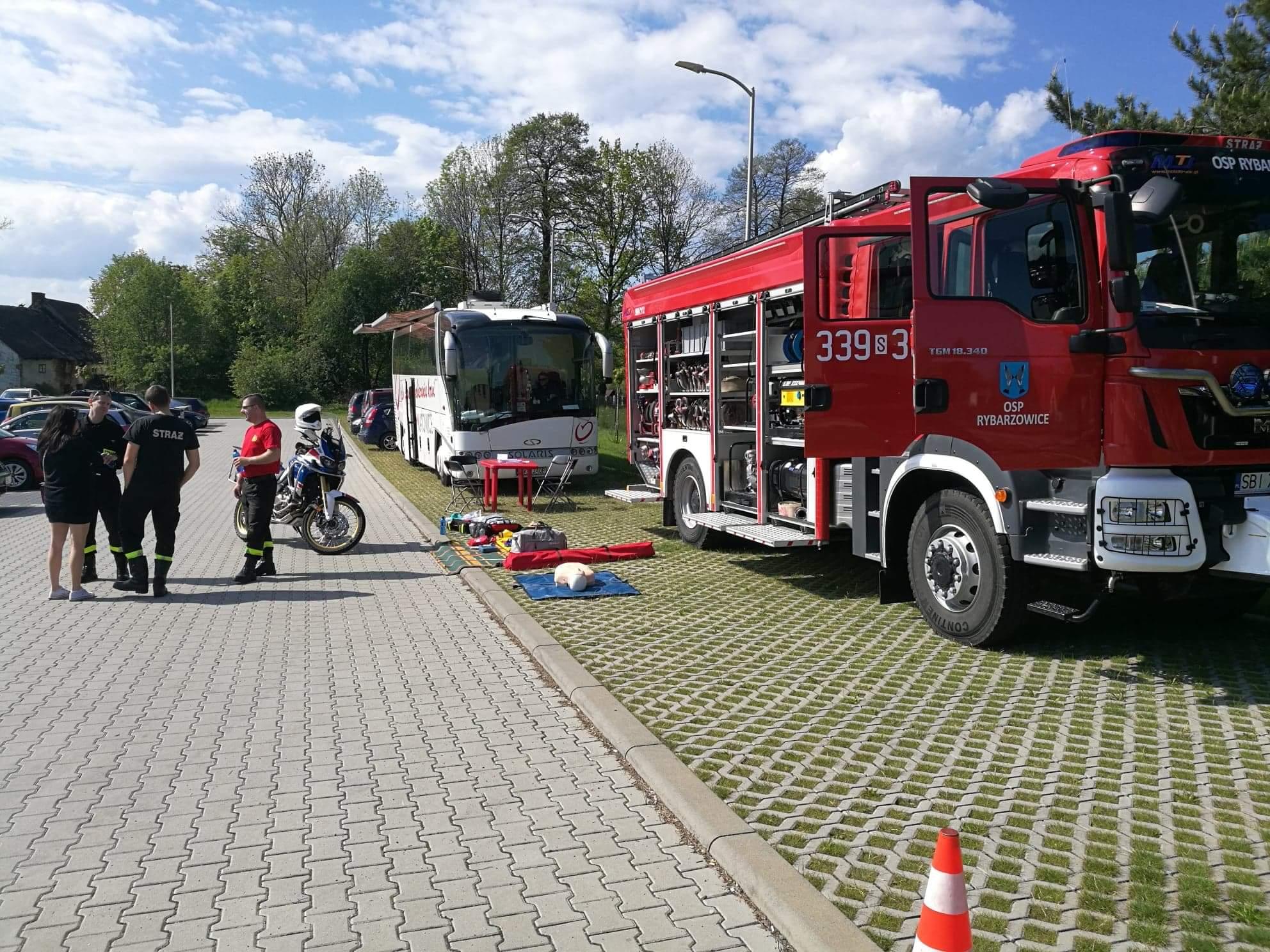 Strażacy prowadzą między sobą rozmowę, obok nich rozłożone są rekwizyty do ćwiczeń z udzielania pierwszej pomocy