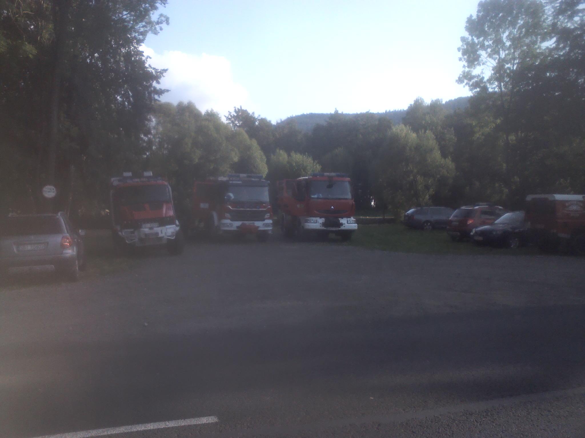 Akcja poszukiwania zaginionej osoby - samochody strażacka i osobowe zaparkowane w miejscu poszukiwań