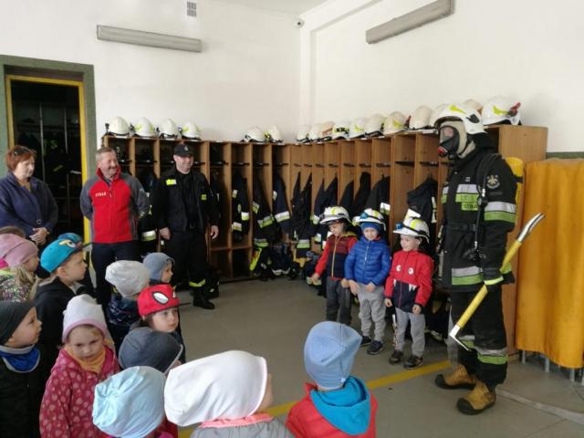 Przedszkolaki w garażu strażnicy przymierzają sprzęt strażacki