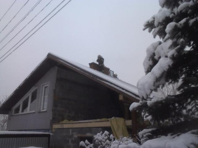 Usuwanie sadzy z komina - na dachu widoczni strażacy wykonujący prace