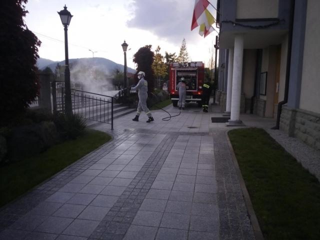 Strażacy odkażają bramę do kościoła