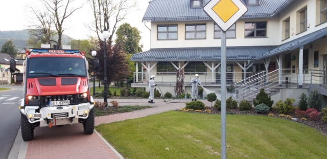 Strażacy odkażają przednie wejście do urzędu gminy