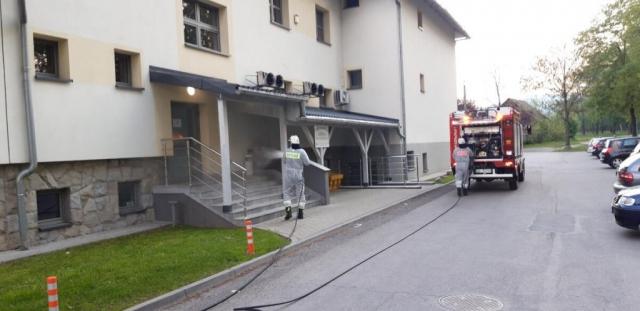 Strażacy odkażają tylne drzwi do urzędu gminy
