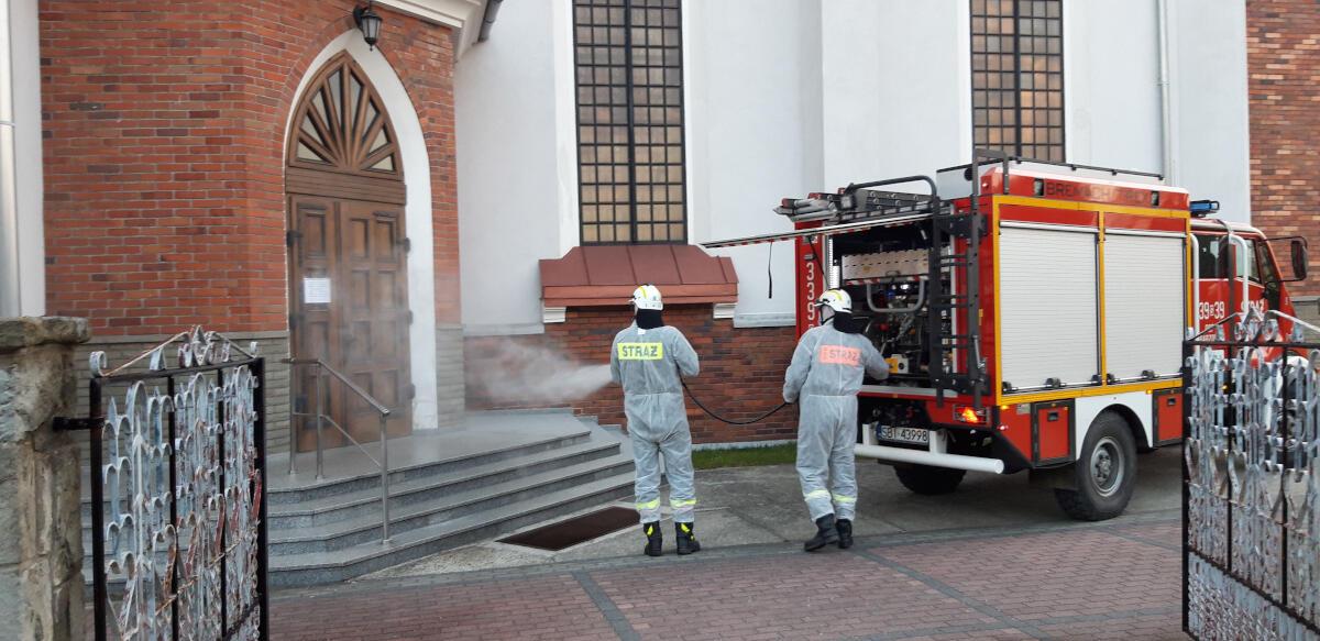 Strażacy odkażają bramę wejściową do kościoła
