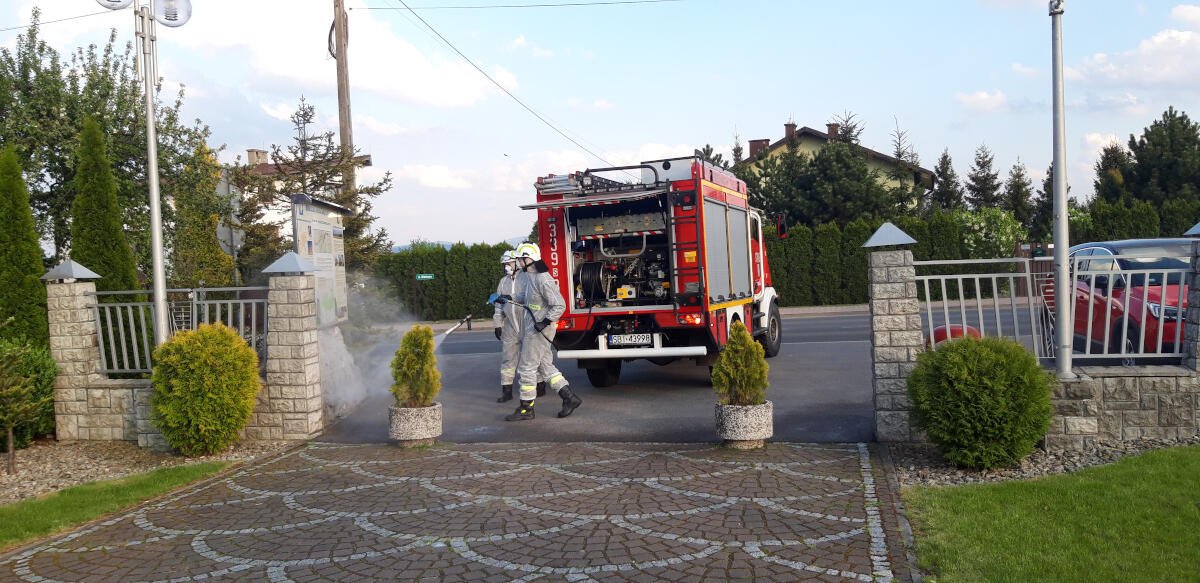 Strażacy odkażają bramę wyjazdową przy kościele