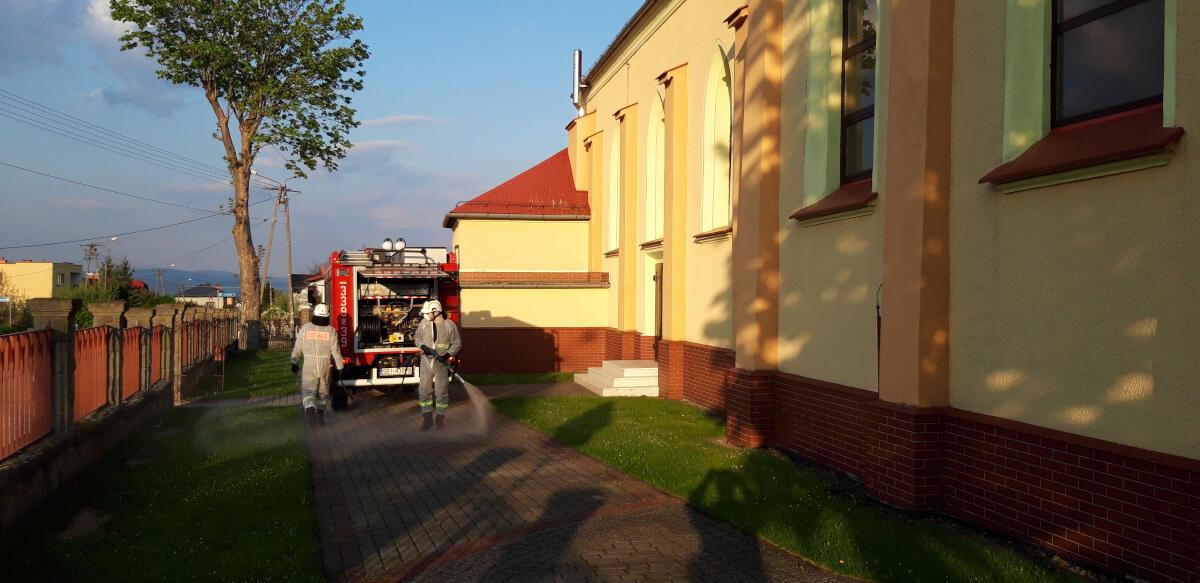 Strażacy odkażają chodnik przy kościele