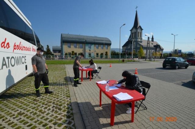 Ochotnicy wypełniają dokumenty - zdjęcie z innej perspektywy