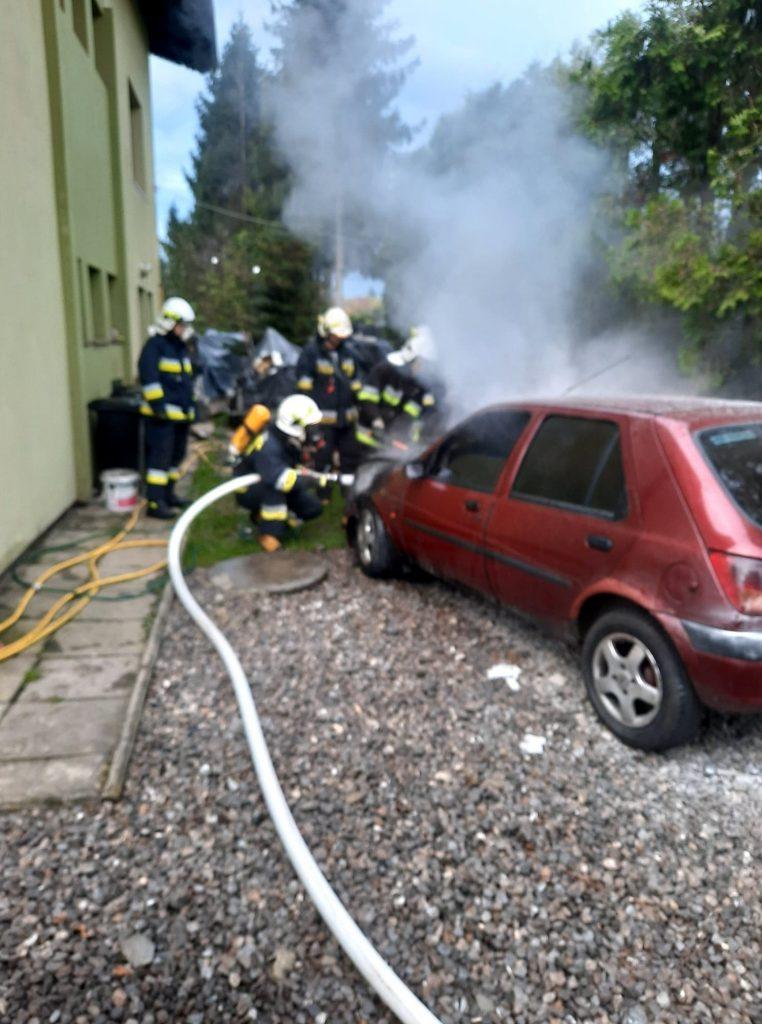 Strażacy ugaszają płonący samochód