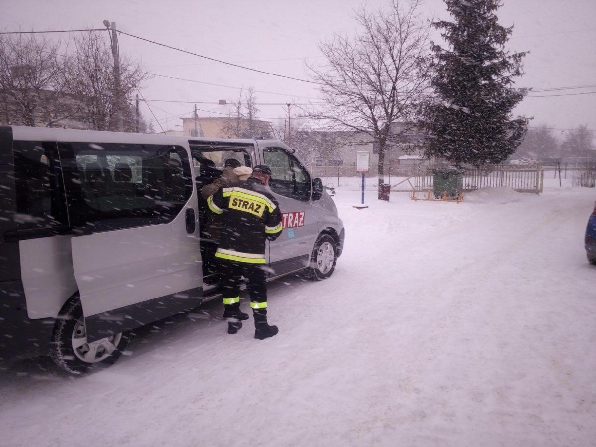 Strażacy transportują osobę na szczepienie