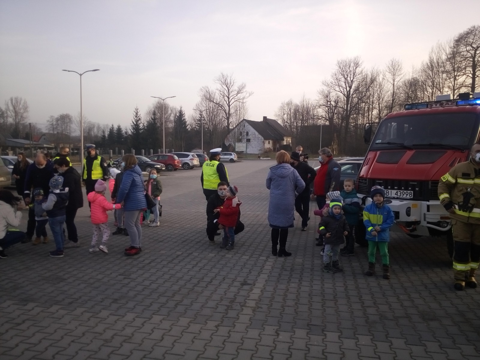 Dorośli i dzieci na placu pozują do zdjęcia