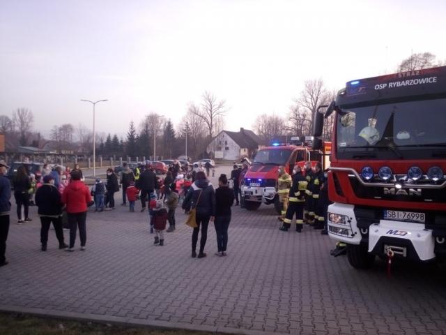 Duża ilość zgromadzonych dorosłych i dzieci, obok pojazdy strażackie