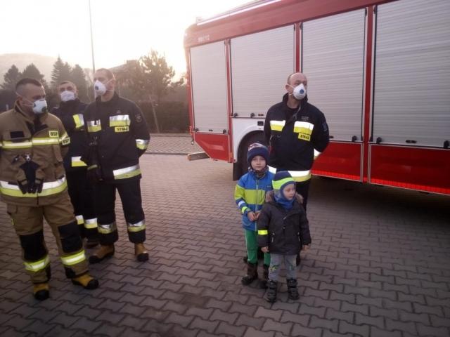 Dzieci pozują ze strażakami, noszą odblaski