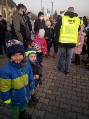 Dzieci uśmiechają się do zdjęcia, w tle rozmawiają osoby