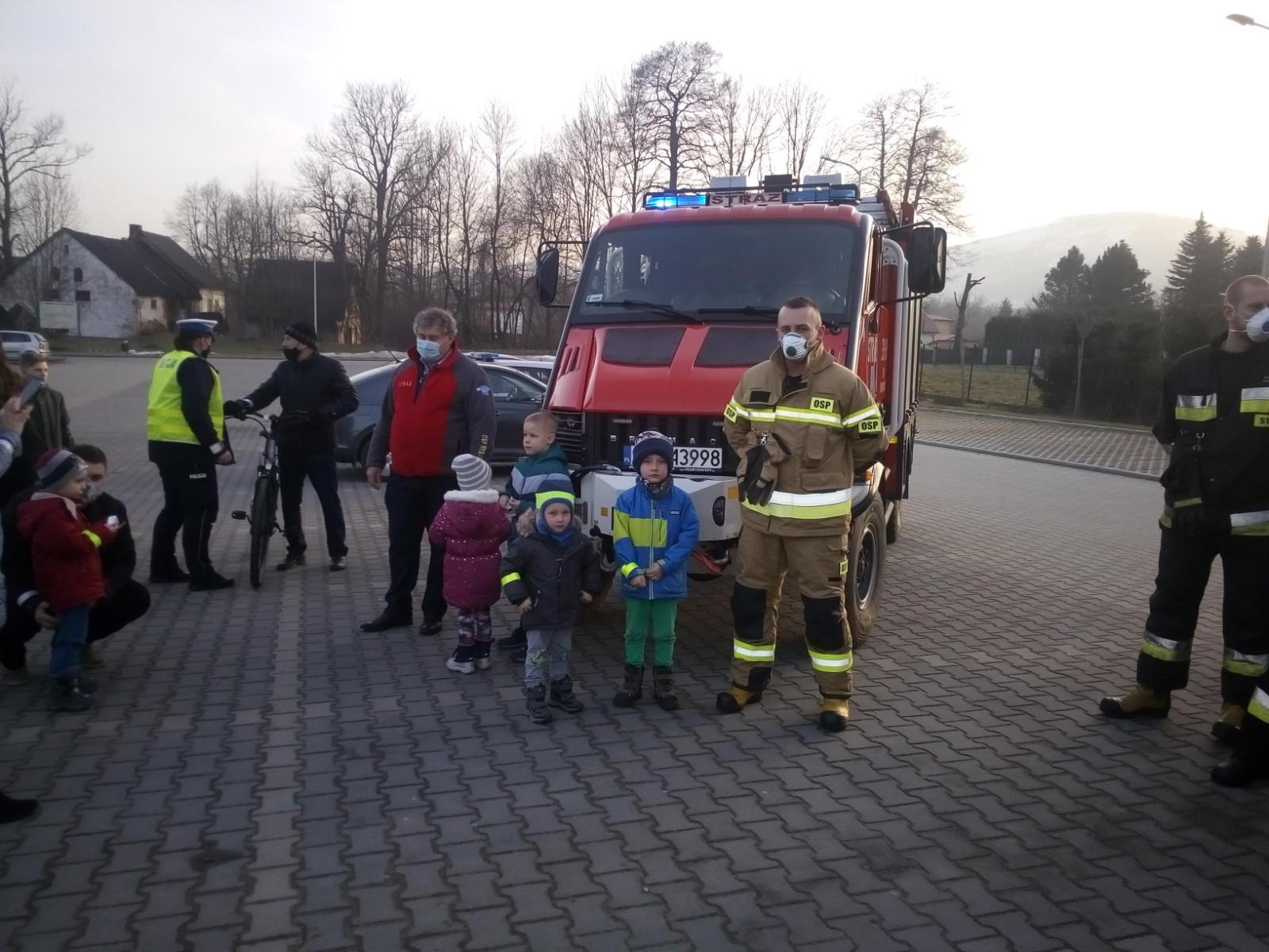 Dzieci pozują do zdjęcia ze strażakiem na tle pojazdu strażackiego