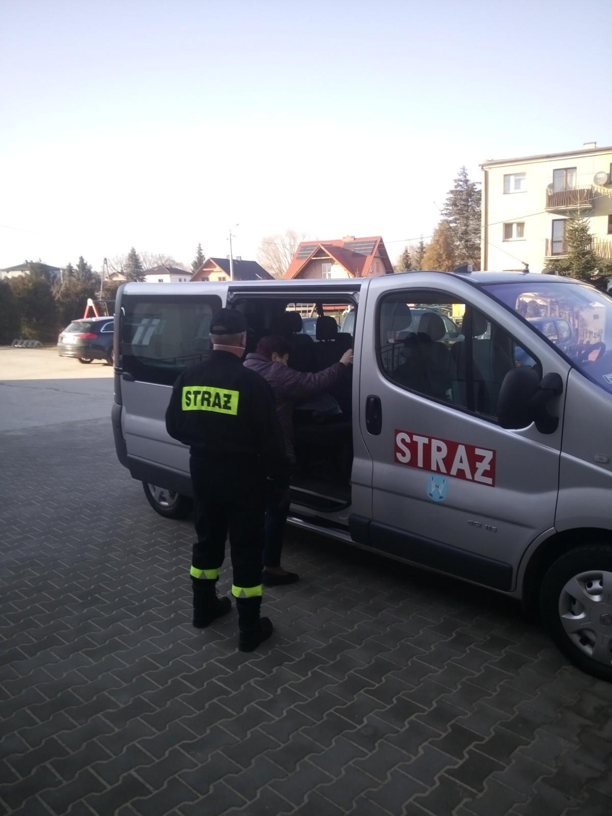 Strażacy pomagają dostać się do pojazdu osobie udającej się do punktu szczepienia