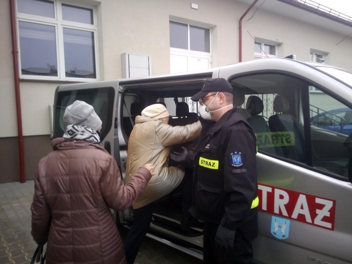 Strażak pomaga dostać się do samochodu osobom udającym się do punktu szczepień