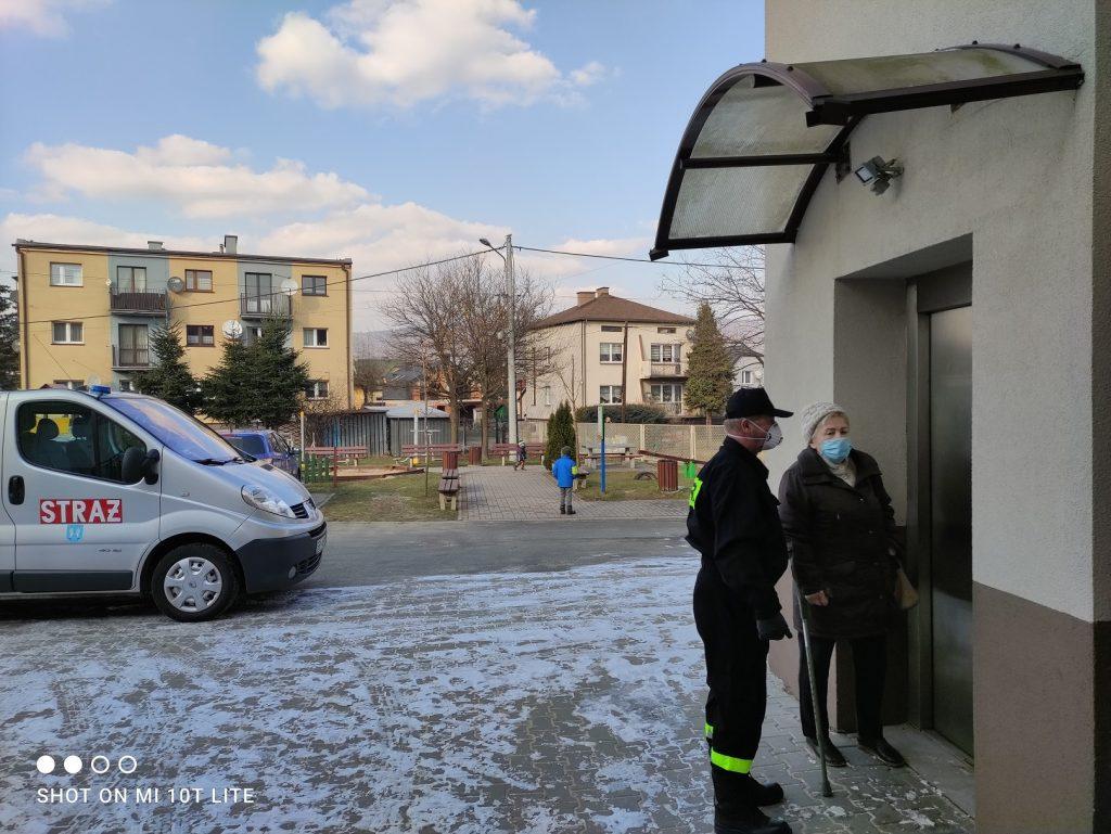 Strażak odprowadza osobę pod windę