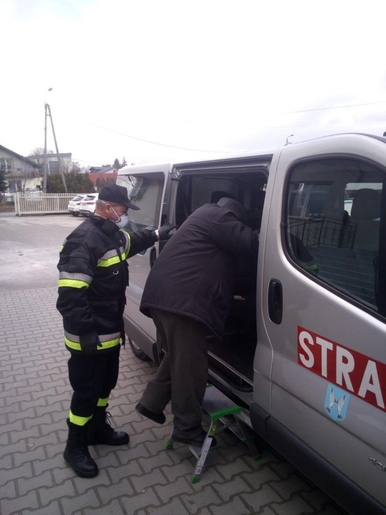 Strażak pomaga osobie udającej się na szczepienie, dostać się do samochodu