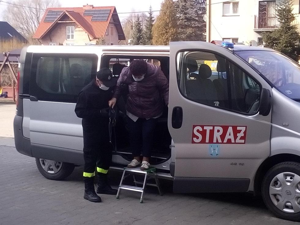 Strażak pomaga opuścić samochód osobie po szczepieniu