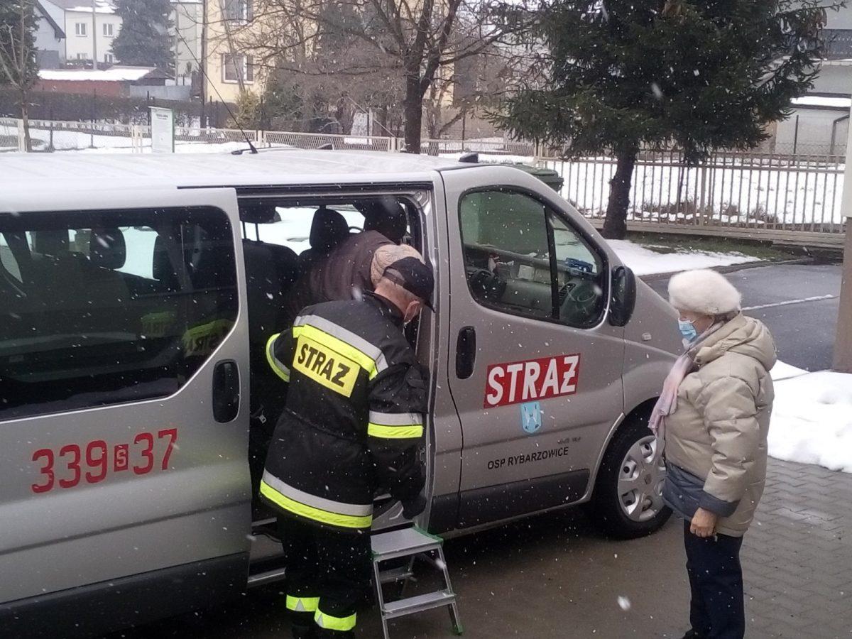 Strażak pomaga opuścić samochód starszej osobie