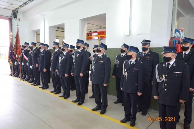 Strażacy stoją na baczność w garażu OSP