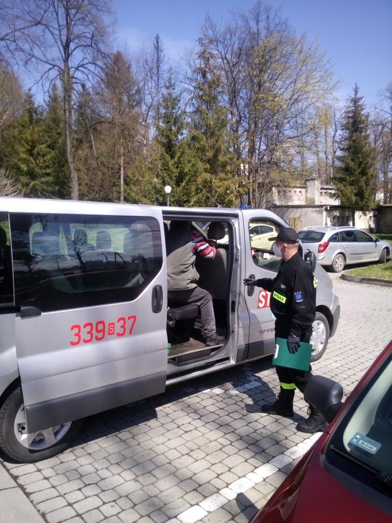 Strażak udziela pomocy osobie transportowanej do punktu szczepień