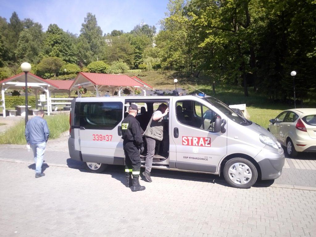 Strażak pomaga wejść do samochodu osobie udającej się na szczepienie